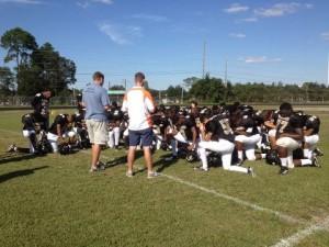 praying with football team